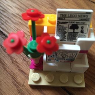 Blumen am Zeitungsständer.